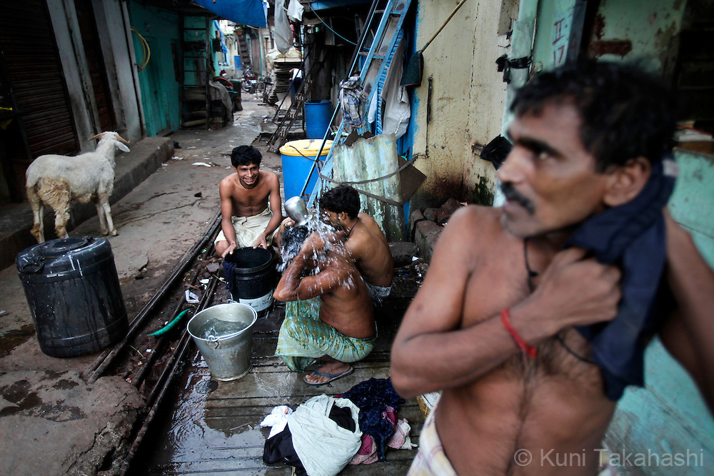 Men bathe at community water tap in Dharavi, India's largest slum, in Mumbai on Oct 26, 2009. The running water is available only 3 hours in the morning and 3 hours in the evening in the community. Due to luck of rainfall in this year's monsoon season, the authorities in Mumbai imposed at least 25 per cent water cut as it faces one of the worst water shortages in its history. Photo by Kuni Takahashi
