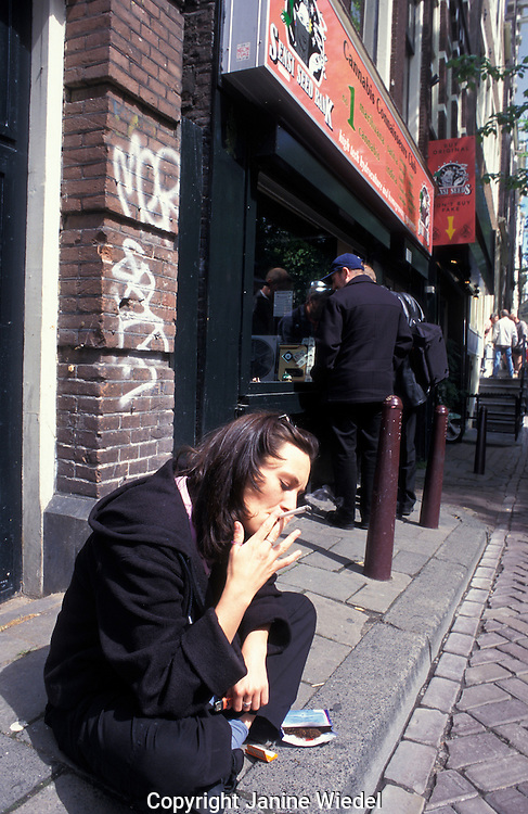 Young girl sitting in the street in Amsterdam smoking a joint.