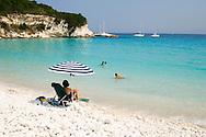 A woman sitting under a beach umbrella on Voutoumi Beach watching her children swim.  Anti-Paxos, Ionian Islands, Greece