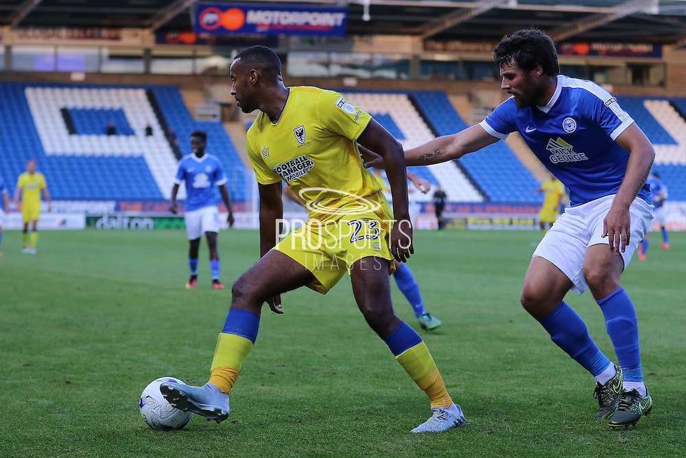 AFC Wimbledon striker Tyrone Barnett (23) shields the ball from Peterborough United midfielder Michael Bostwick (4) during the EFL Cup match between Peterborough United and AFC Wimbledon at ABAX Stadium, Peterborough, England on 9 August 2016. Photo by Stuart Butcher.