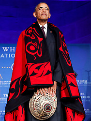 US President Barack Obama receives a traditional blanket and hat during a blanketing ceremony at the 2016 White House Tribal Nations Conference at the Andrew W. Mellon Auditorium, September 26, 2016, Washington, DC. The conference provides tribal leaders with opportunity to interact directly with federal government officials and members of the White House Council on Native American Affairs. (Pool/Aude Guerrucci)