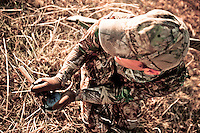 TURKEY HUNTER WEARING REALTREE AP CAMO CAMOUFLAGE CALLING FOR TURKEYS USING A SLATE CALL