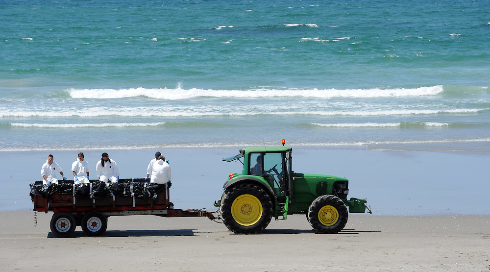 Crews still check the beach after the announcement that most of the beaches previuosly closed by the oil spill off the stricken container ship, Rena are now open for public use, Mt Maunganui, New Zealand, Tuesday, November 15, 2011. Credit:SNPA / Ross Setford