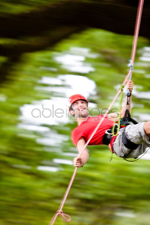 Man dangling from a rope suspended mid air - blurred motion
