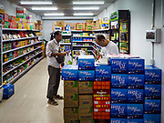 """14 FEBRUARY 2019 - SIHANOUKVILLE, CAMBODIA:  A Chinese man buys groceries in a Chinese owned convenience store in Sihanoukville. There are thousands of Chinese workers in Sihanoukville who work to support the casino and hotel industry in the town and thousands of other Chinese migrants have moved into Sihanoukville and opened businesses that cater to the workers. There are about 80 Chinese casinos and resort hotels open in Sihanoukville and dozens more under construction. The casinos are changing the city, once a sleepy port on Southeast Asia's """"backpacker trail"""" into a booming city. The change is coming with a cost though. Many Cambodian residents of Sihanoukville  have lost their homes to make way for the casinos and the jobs are going to Chinese workers, brought in to build casinos and work in the casinos.      PHOTO BY JACK KURTZ"""