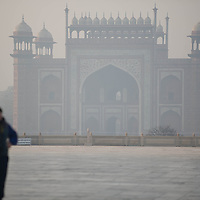 Feb 12, 2013 - A tourist walks past the Mughal architecture of the Taj Mahal&rsquo;s mosque through the smog in Agra, India. To cut back on pollution, cars and buses are not allowed to drive to the Taj Mahal but to a parking lot about 1.5 miles away, where visitors can take battery-run buses or horse-drawn carriages to reach the monument.<br /> <br /> Story Summary: It is said that the battle over global warming is to be won or lost in Asia. With growing populations and new economic boom in the global markets across Asia countries like India, Nepal and Cambodia have to grapple with the success and the environmental disaster that comes with ramped up production in unchecked or unregulated industries to compete in todays marketplace. The catastrophic air pollution makes for new problems to be dealt with such as a future health crisis, quality of life issues and the tarnished image of reduced visibility to world heritage sites for tourism.