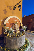 An altar decorated with flowers and candles on a public fountain celebrating El Viernes de Dolores during Holy Week March 23, 2018 in San Miguel de Allende, Mexico. The event honors the sorrow of the Virgin Mary for the death of her son and is an annual tradition in central Mexico.