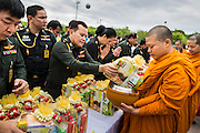"22 JULY 2014 - BANGKOK, THAILAND: Thai Army officers make merit by presenting alms to Buddhist monks during a merit making ceremony on Sanam Luang in Bangkok. Hundreds of Thai military officers and civil servants attended a Buddhist chanting service and merit making ceremony to mark the 2nd month anniversary of the May 22 coup that deposed the elected civilian government and ended nearly six months of sometimes violent anti-government protests. The ruling junta said the ceremonies Tuesday were the kickoff to a ""Festival to Bring Back Happiness of the People of the Nation."" There will be free concerts, historical pageants and movies at Sanam Luang, a large parade ground near the Ministry of Defense in Bangkok.    PHOTO BY JACK KURTZ"