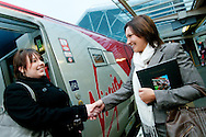 Two business women greeting each other shaking hands at the open door of a Virgin Pendolino train