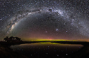 An 18-image panoramic of the beautiful Milky Way arching over a fading Aurora Australis in Southland, New Zealand.