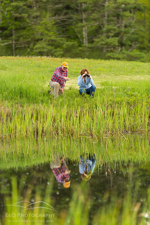 A couple birdwatching in a field in York, Maine.