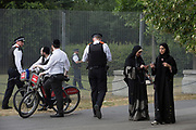 Jewish men, Muslim ladies with UK Met police officers who guard a temporary perimeter fence encircling Winfield House, the official residence of the US Ambassador during the visit to the UK of US President, Donald Trump, on 12th July 2018, in Regent's Park, London, England.