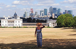 © Licensed to London News Pictures. 01/08/2018<br /> Greenwich, UK. A woman shelters in the shade on Greenwich Park, in front of the city of London, as a heatwave is set to return to the UK. Photo credit: Grant Falvey/LNP