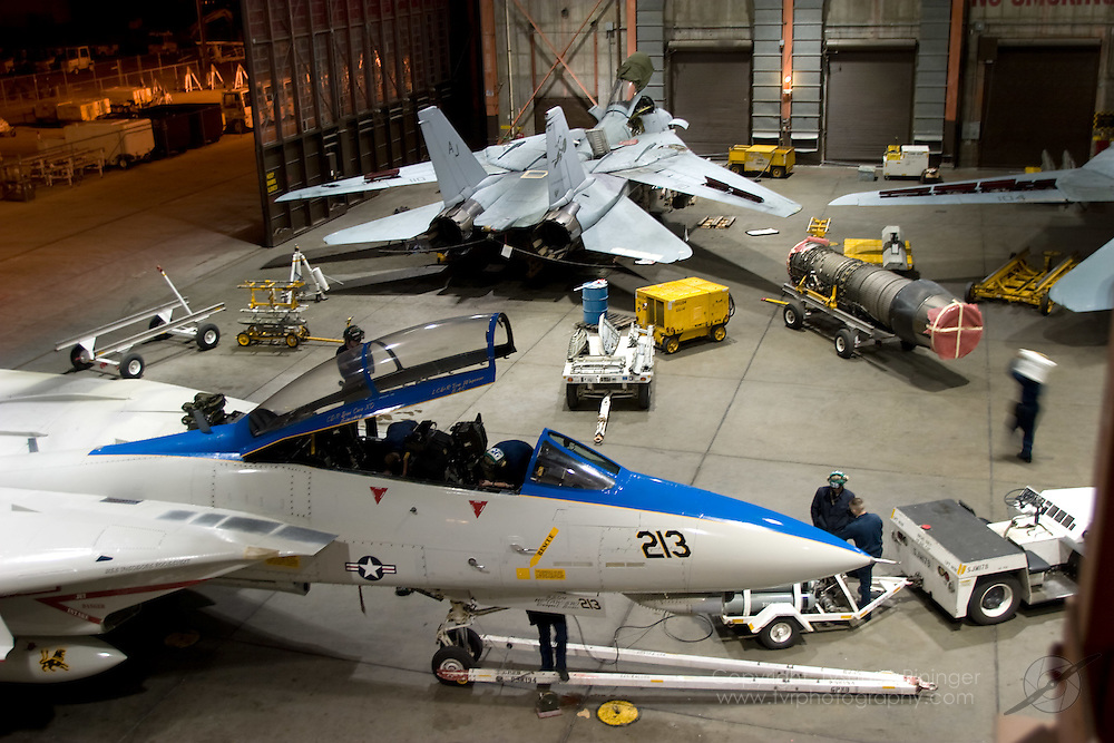 VF-213's retro-painted F-14D is rolled into the hangar at NAS Fallon for some electrical work.  In the background, an F-14D from VF-31 is also being worked on.  Workups at Fallon provide the Airwing's aircrew to experience maintenance training at remote locations.