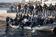 ITALY, Lampedusa :Tunisian migrants are helped as they they fell into the water after  they arrived  in Lampedusa on March 27, 2011. Copyright Christian Minelli.