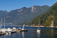 "The sailboat ""Salt Peter"" comes in to dock at Sewell's Marina.  Photographed from the Public Dock at Horseshoe Bay in West Vancouver, British Columbia, Canada. Howe Sound and Saint Mark's Summit, Unnecessary Mountain, Mount Harvey, Brunswick Mountain (of the  Pacific Ranges and Coast Mountains) are in the background."