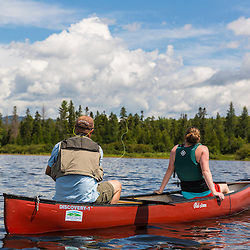 A man and woman canoeing on Saddleback Lake in Dallas Plantation, Maine. High Peaks region near Rangely. Fly-fishing.