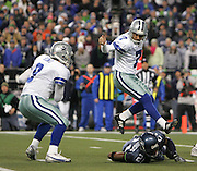 Dallas Cowboys quarterback Tony Romo, left, runs with the ball as kicker Martin Gramatica jumps over Seattle Seahawks Kelly Jennings on the botched field goal attempt during the NFL football game in an NFC wild-card playoff game on Saturday, Jan. 6, 2005 in Seattle. (AP Photo/Kevin P. Casey)