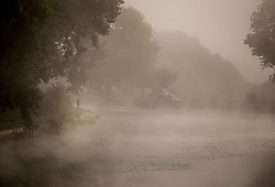 © Licensed to London News Pictures. 11/09/2016. Reading, UK.  A dog walker looks out over a  misty river Thames in early morning sunshine near Reading. A period of warm weather is expected in mid September.Photo credit: Peter Macdiarmid/LNP