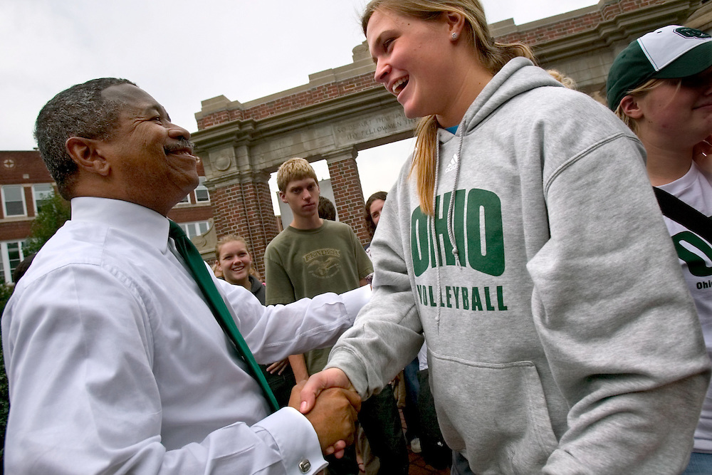 """Ohio University President Roderick McDavis greets freshman Ellen Herman and other members of the 2006 freshman class as they file through the College Gate...OPENING SCHOOL IN STYLE -- Members of the 2006 freshman class at Ohio University will get their college careers off on the right foot, both literally and figuratively, with the traditional march through the College Gate at approximately 3:15 p.m. Monday, Sept. 4. Following the President's Convocation at 2:30 p.m. in the Convocation Center, the new Bobcats will follow """"The Most Exciting Band in the Land,"""" the Marching 110, from the Convo for the trek up Richland Avenue toward the College Green as they officially begin their college careers..Once on the College Green, representatives of more than 200 student organizations across campus will have displays set up to introduce the newest Ohio University students to the many ways to become actively involved in campus life..It is a colorful tradition that captures the spirit of college life. It also makes for tremendous photo and video opportunities for a unique twist on the conventional moving-in activities as the academic years of schools, colleges and universities across the state hit full stride over Labor Day Weekend."""