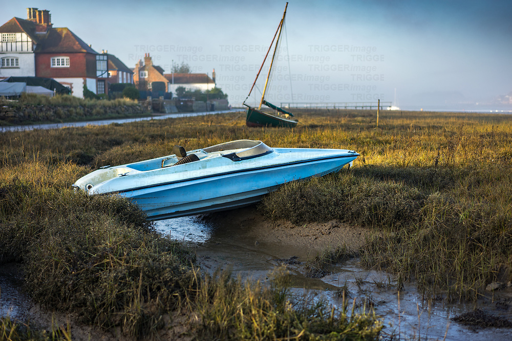 View across the estruary in Bosham looking towards old cottages in winter with a dinghy high and dry on mudflats