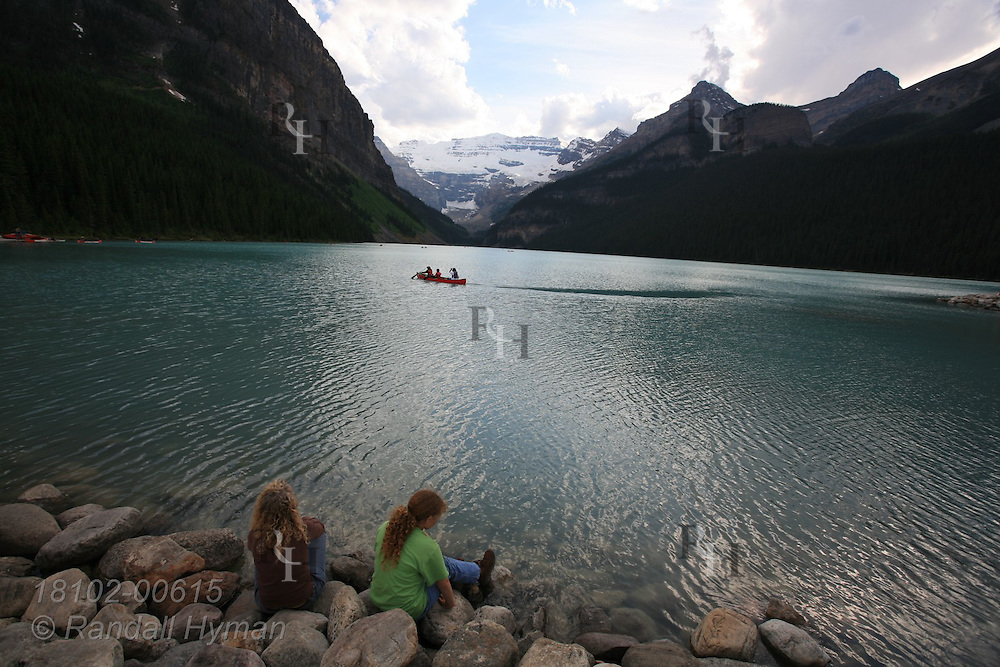Mother and daughter sit on rocky lakeshore enjoying the tranquility of Lake Louise amid the soaring mountains of Banff National Park in the Canadian Rockies; Alberta, Canada.