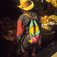 Central America, Latin America, Guatemala, Chichicastenango. Local man shopping for fruit at the Chichicastenango market.