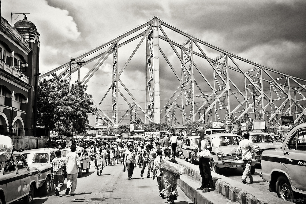 Crowds enter and depart Howrah train station at the base of Howrah Bridge in Kolkata (Calcutta), India. Converted to black and white using Silver Efex Pro.