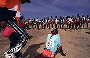 Exhausted runner collapses at the end of a cross country race. The best will have the lucrative opportunity of racing abroad.