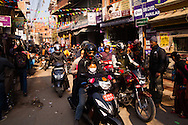 Commuters head towards the early morning sunshine as they make their way to work on foot, bicycle, rickshaw and scooter through the narow streets of the Thamel District in Kathmandu, Nepal.