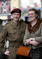 © Licensed to London News Pictures. 12/10/2014. Pickering, UK The annual wartime weekend in Pickering, North Yorkshire. People dress in 1940s period themed outfits and attend parades through the small Yorkshire town which has a traditional steam railway as would have been used in the 1940s. // Pictured:  Craig Dawson and Sophie Dawson from Thirsk get into the spirit of the event. Saturday 11th October 2014. Photo credit :  HARRY ATKINSON/LNP