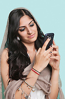 Young Asian woman in traditional clothing text messaging against blue background