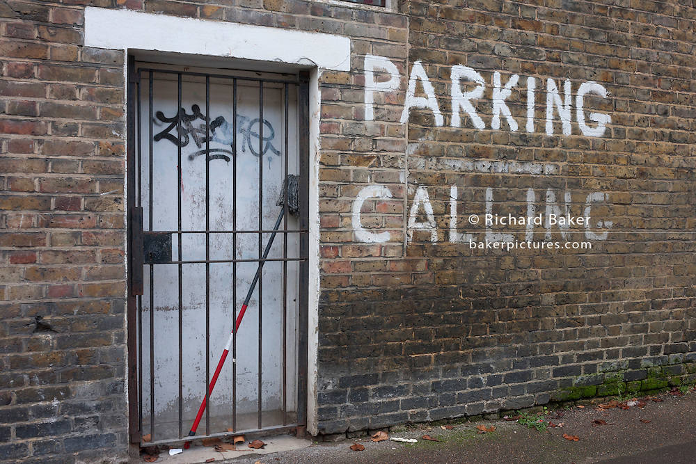 A grilled doorway and painted no parking message on 4th January, London borough of Southwark, England.