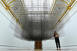 """© Licensed to London News Pictures. 16/09/2019. LONDON, UK. A staff member poses next to """"""""Matrix III"""", 2019, by Antony Gormley. Preview of a new exhibition by Antony Gormley at the Royal Academy of Arts.  The show bring together existing and specially conceived new works from drawing to sculptures to experimental environments to be displayed in all 13 rooms of the RA's Main Galleries 21 September to 3 December 2019.  Photo credit: Stephen Chung/LNP"""