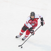 Matt Benning #5 of the Northeastern Huskies in action during the Frozen Fenway game between The Northeastern Huskies and The UMass Lowell Riverhawks at Fenway Park on January 11, 2014 in Boston, Massachusetts.
