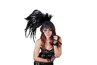 Portrait of young fashion model wearing feathered headdress over white background