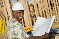 Middle-aged man in hard hat holding blueprint in front of house construction site