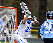 Bedford High School senior goalie Noah Gilbert knocks away a shot during the game against Triton at home in Bedford, April 19, 2018. Bedford fell to Triton, 12-6.   [Wicked Local Photo/James Jesson]