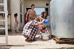 © Licensed to London News Pictures. Hamdaniyah, Iraq. 26/07/2014. Christian refugee Ra'id Samir Kamal (45), formerly a driver in Mosul, washes his youngest daughter after Kurdish Zeravani soldiers distributed fresh supplies of drinking water to refugee families living in partially built houses in Hamdaniyah, Iraq. Samir left Mosul on Friday the 18th of July when Islamic State fighters issued an ultimatum to the city's Christian community. When the family left they were forced to pay a tax for their car, their son (19) was threatened at knifepoint to ensure they handed over all of their possessions including family photographs.<br /> <br /> <br /> Having taken over Mosul Iraq's second largest city in June 2014, fighter of the Islamic State (formerly known as ISIS) have systematically expelled the cities Christian population. Despite having been present in the city for more than 1600 years, Christians in the city were given just days to either convert to Islam, pay a tax for being Christian or leave; many of those that left were also robbed at gunpoint as they passed through Islamic State checkpoints.. Photo credit : Matt Cetti-Roberts/LNP