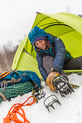 A woman prepares for a hike while winter camping in New Hampshire's White Mountains. Randolph Community Forest.