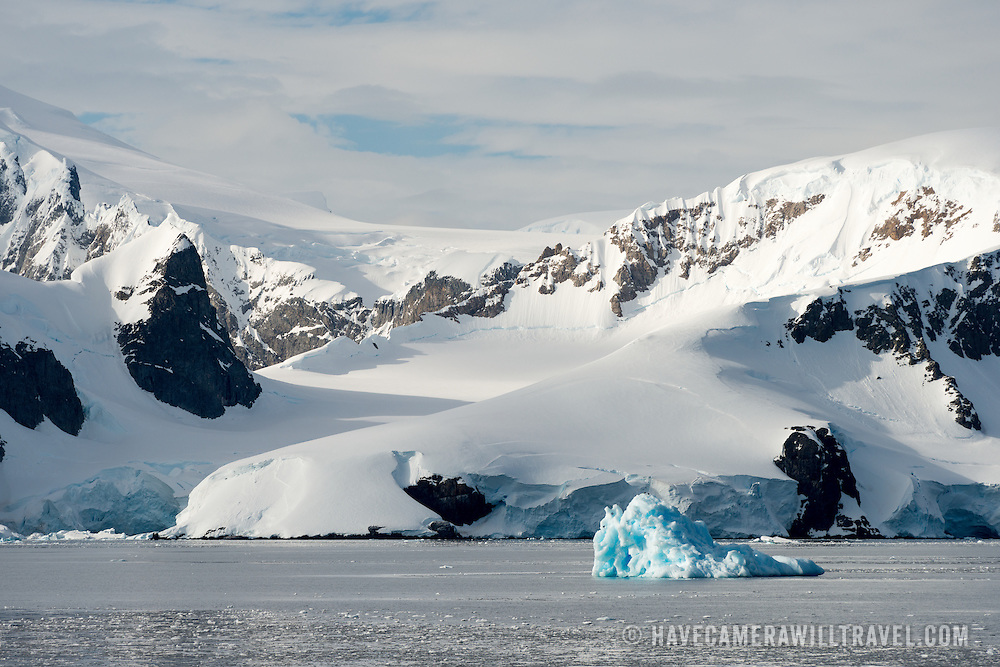A bright blue iceberg of glacier ice floats by the mountains lining the Gerlache Strait on the western side of the Antarctic Peninsula.