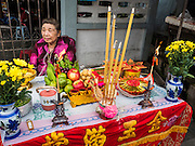 "23 JUNE 2015 - MAHACHAI, SAMUT SAKHON, THAILAND:  A woman sits at the altar she built for the City Pillar Shrine while she waits for the procession to pass her in Mahachai. The Chaopho Lak Mueang Procession (City Pillar Shrine Procession) is a religious festival that takes place in June in front of city hall in Mahachai. The ""Chaopho Lak Mueang"" is  placed on a fishing boat and taken across the Tha Chin River from Talat Maha Chai to Tha Chalom in the area of Wat Suwannaram and then paraded through the community before returning to the temple in Mahachai.  PHOTO BY JACK KURTZ"