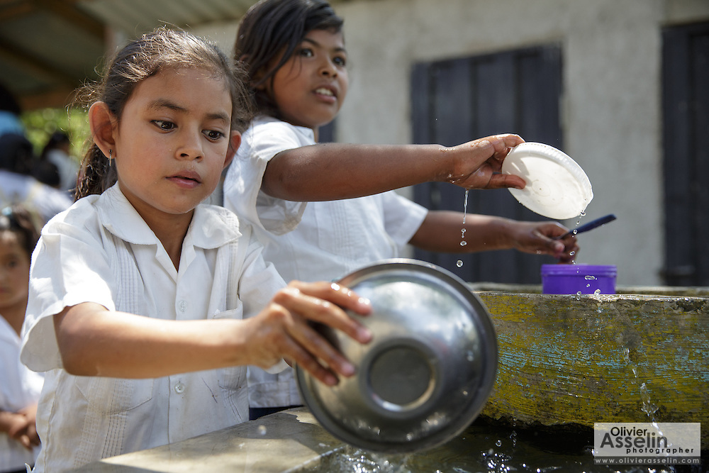 Girls wash their plates after having lunch at the primary school in the town of Coyolito, Honduras on Wednesday April 24, 2013.