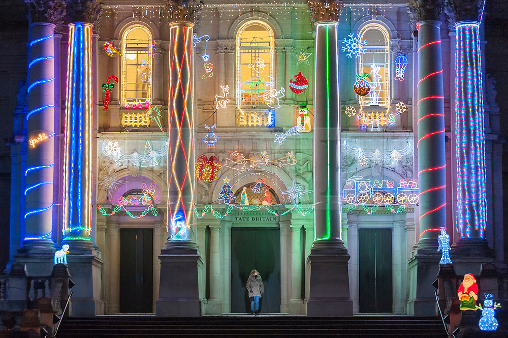 "© Licensed to London News Pictures. 01/12/2017. London, UK.  Alan Kane's new work, ""Home for Christmas"", is unveiled at Tate Britain.  ""Home for Christmas"" transforms the exterior of the gallery into a glowing display of off-the shelf decorations with an arrangement of LED Santas, reindeer, snowmen and Christmas trees, along with 'Merry Christmas' and 'Santa Stop Here' signs.  The artwork will be switched on daily from 2 December 2017 to 6 January 2018.  Photo credit: Stephen Chung/LNP"