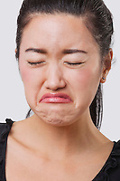 Close-up of young Chinese woman crying over white background