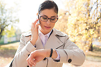Businesswoman checking time while using smart phone at park