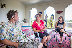 """Fifth generation Bahá'í Parvin Esfahani with husband Woody Stanwood, left, and daughter Aneesa Machin, right, reflect on how members of her family have risked persecution, jail and death in Iran for over thirty years.  While the rest of her family have fled the country, her sister, brother-in-law, and two nephews are currently facing prosecution but refuse to leave their home.  """"I'll tell my sister this,"""" she says, """"This will bring them so much joy....they will tell the whole community and tell each other 'people are still thinking about us...they care'"""".   Local and visiting members of the Bahá'í faith commemorate the anniversary of the Mártyrdom of the Báb, during which the prophet was executed by a firing squad in Iran for delivering his teachings.  The faith, which emphasizes the oneness of God, religion, and humanity celebrates diversity and boasts  members of all races, religious backgrounds, and cultural heritages.   Bahá'í National Center.  10 July 2015.  © Aisha-Zakiya Boydraces, religious backgrounds, and cultural heritages.   © Aisha-Zakiya Boyd"""