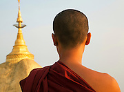 Monk and golden pagoda spire. Kyaiktiyo Pagoda. The Golden Rock Buddhist religious shrine, Myanmar.