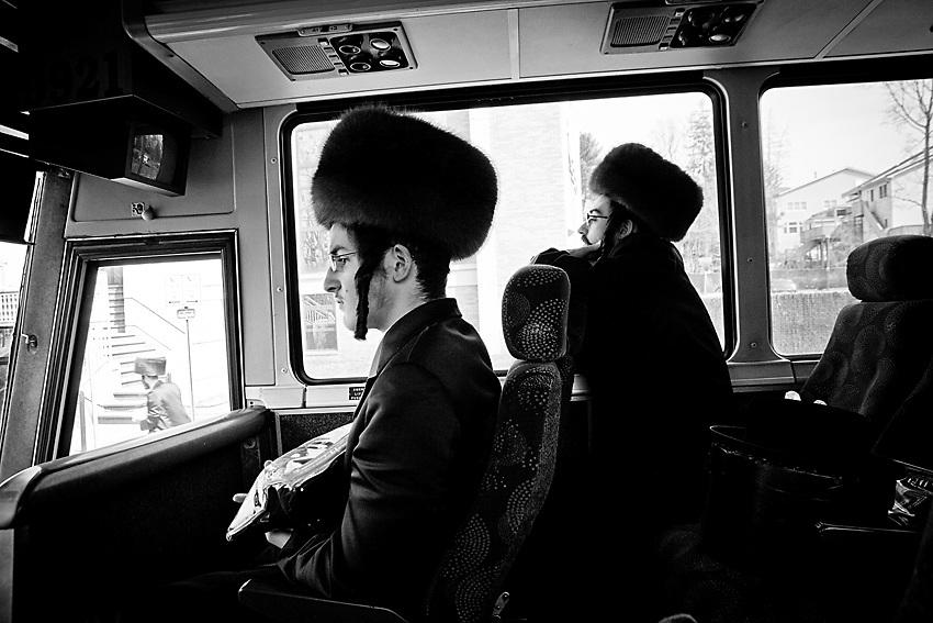 L'autobus che va da Williamsburg a New Square, Upstate e` un autobus della linea Monsey Trail ed e` severamente vietato per gli autisti e/o gli impiegati della linea di bus utilizzare la &quot;mechiza&quot;, il divisorio tra uomini e donne che si vede nella foto per motivi di discriminazione razziale. <br /> Nei gruppi di ebrei ultra-ortodossi come sono quelli di Monsey o New Square, la divisione tra uomini e donne e` obbligatoria. Il divisiorio, nascosto di solito in uno degli sportelli del bus, e` quindi affisso all`inizio di ogni viaggio dal primo uomo ebreo ortodosso a salire sull`autobus. <br /> Verra` poi tolto dall`autista alla fine della corsa per poi essere riposizionato di nuovo dal prossimo passeggero. Lo stato di New York proibisce severamente quest'usanza per via del messaggio di segregazione razziale tra uomini e donne implicato da tale usanza. Quindi il rituale e` a rischio e pericolo dei passeggeri che pero` non sembrano avere alcun problema in merito. Foto scattata il 16 Marzo 2014 durante la festa di Purim, il carnevale ebraico.