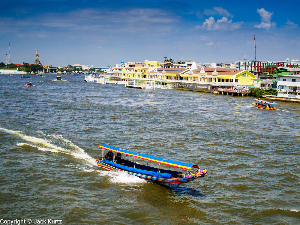 """28 OCTOBER 2014 - BANGKOK, THAILAND: Passenger boats on the Chao Phraya River pass the Yodpiman Flower Market, also known Pak Khlong Talat, in Bangkok. The market is being renovated and gentrified as a """"heritage mall."""" The first phase of the renovation are the new yellow buildings along the river.     PHOTO BY JACK KURTZ"""